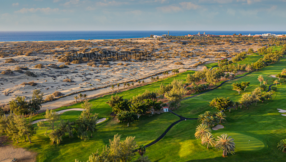 Vista aérea del campo de golf de Maspalomas con  los hoyos 6 y 12 en primer plano y al fondo la playa, dunas y faro de Maspalomas al sur de la isla de Gran Canaria
