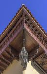 Escultura en piedra bajo el balcón de madera haciendo esquina en el lado norte de la casa de Colón de Las Palmas y de estilo arquitectónico canario mostrado en las rutas de fotografía por Vegueta