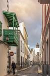 Vista oblicua hacia las torres de la catedral y balcones típicos de la arquitectura popular en Canarias en la calle de San Marcos en Vegueta donde el sol del atardecer nuboso tiñen de dorado las últimas nubes de un día lloviznas en Vegueta