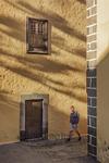 La luz oblicua del atardecer proyecta sombras y remarca texturas sobre la pared de una casa de arquitectura tradicional canaria al paso de un turista en sus rutas fotográficas por el antiguo barrio capitalino de Vegueta de la ciudad de Las Palmas